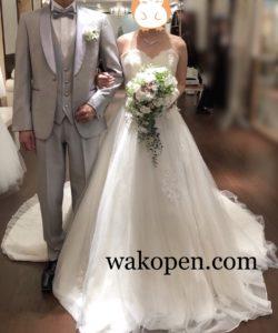 チュール生地のウェディングドレスと明るいグレーのタキシード